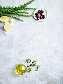 Kräuter, Oliven, Zitronen, Knoblauch und Olivenöl auf weißem Untergrund