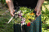 A woman holding a plate of freshly harvested herbs and flowers