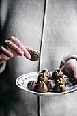 Frau hält Teller mit veganen Dattel-Mandel-Trüffeln (Raw Food)