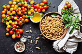 Zutatenstilleben mit Fusilli, Kirschtomaten, Olivenöl, Salz und Pfeffer