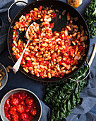 Tomatoes, cannellini beans and onions in a pan beside a bunch of silverbeet and a bowl of cherry tomatoes