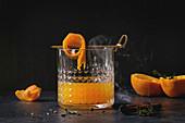 Whiskey mit Orangensaft serviert mit Orangenschalenspieß und rauchender Zimtstange