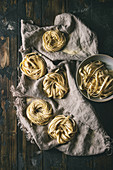 Variety of italian homemade raw uncooked pasta spaghetti and tagliatelle with semolina flour on linen cloth
