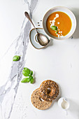 Bowl of vegetarian pumpkin carrot soup served with herbs, spoon, jug of cream, bagel bread, black pepper, salt