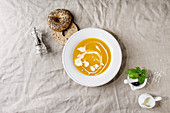 Plate of vegetarian pumpkin carrot soup decorated by cream served with herbs