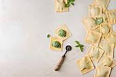 Homemade raw uncooked italian pasta ravioli staffed by spinach ricotta, basil leavrs, pasta cutter
