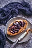 Brotscheibe mit Erdnussbutter und Blaubeermarmelade