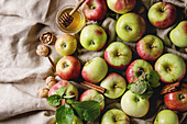 Ripe organic gardening green red apples with leaves, walnuts, cinnamon and jar of honey