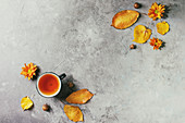 Cup of hot tea decorated by yellow autumn leaves, aster flowers and acorns over grey texture background