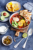 Chili con carne with avocado, corn and pancakes