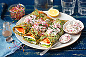 Spinach pancakes with camembert, smoked salmon and red radishes with yogurt