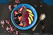 Beet and chia seeds pudding served with berries, avocado and pine nuts