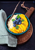 Millet breakfast with fresh mango and bluberries