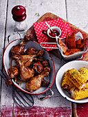 Grilled chicken drumsticks, corn on the cob and sweet potato wedges