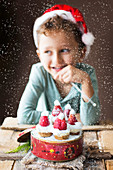 Little Smiling Boy with Mini Cheesecake with 'Santa' Strawberry Hats on a Tin