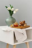 Frühstückshörnchen mit Marmelade neben Blumenvase mit Tulpen auf Tischchen