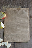 Mehrere Blätter Papier daneben Zucker und Apfelstücke