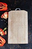 A wooden chopping board and red peppers