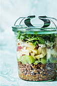 A layered spelt, apple and celery salad in a jar