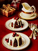 Christmas mini puddings topped with rum sauce ans cranberries