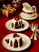 Kleine englische Christmas Puddings serviert mit Rumsauce und Cranberries