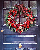 Christmas wreath on grey door with golden pears and red apples fruits and berries