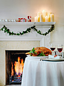 Roast Goose with sage on table by fireplace