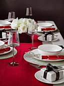 Table set for Christmas dinner witha red white and black theme