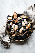 Top view with frozen mussels on white marble background