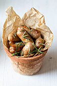 Sausages with rosemary served in a terracotta flower pot