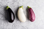 Three different coloured aubergines