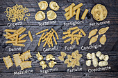 Various types of pasta with labels on a wooden background