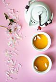 Teeschalen, Teekanne und Blütenblätter