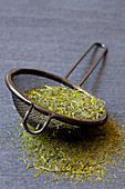 Japanese green tea leaves in a metal strainer