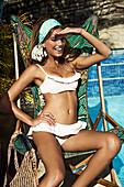 Junge brünette Frau in weißem Bikini mit Kopftuch sitzt in einer Liege neben einem Pool