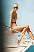 Junge blonde Frau mit kurzen Haaren im gemusterten Badeanzug sitzt auf Boot