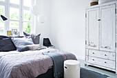 Doppelbett mit Tagesdecke und Kleiderschrank mit abgeblätterter Farbe im Schlafzimmer