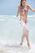 Junge brünette Frau im gestreiften Bikini am Strand