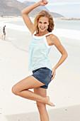 Junge blonde Frau im hellblauen Shirt und Jeansrock am Strand