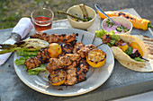 Grilled tandoori chicken skewers with a beetroot dip and lemons