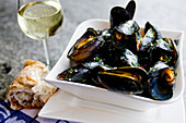 Mussels served with bread and a glass of white wine