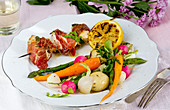 Chicken skewers wrapped in a Parma ham with a warm vegetable salad