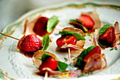 Strawberry skewers with lomo and mint