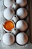 Eier, ganz und aufgeschlagen, im Eierkarton