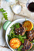 Grilled lamb meatballs with halved lemons