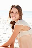 Junge brünette Frau im beigen Shirt am Strand