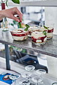 Cheesecakes in glasses being garnished with mint