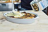 Moussaka mit Sauce bedecken