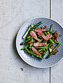 Marinated beef strips on green asparagus and dates