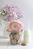 Cookies with chocolate icing in a mason jar decorated with rose blossoms